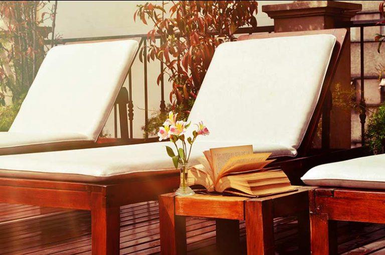 Three Lounge Chairs White Cushions Book Flower
